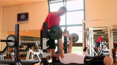 vzpírání : Young man doing weigths on a bench press with the help of the mature instructor at gym. Athletic man is lifting weights with her personal trainer at the gym.