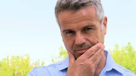 amadurecer : Confident mature man smiling and looking at camera. Satisfied leadership smiling and looking at camera outside. Portrait of an happy man with grey hair and shirt posing outdoor. Stock Footage