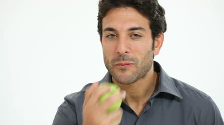 man eating : Young man eating green apple isolated on white background. Smiling guy bitten a healthy apple. Portrait of happy man eating a fresh apple and looking at camera. Stock Footage