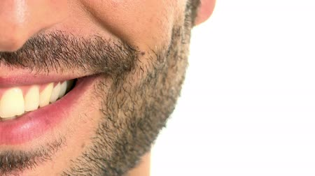 детеныш : Close up of a smiling teeth isolated on white background. Detail of a smile man with beard. Young smiling on white background. Beautiful smile of a boy.