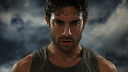 Young exhausted latin man looking at camera during a break of his outdoor jogging training. Portrait of a sweaty man focuses and looking at camera with a storm in the background.  Power and concentration of a sporty guy.