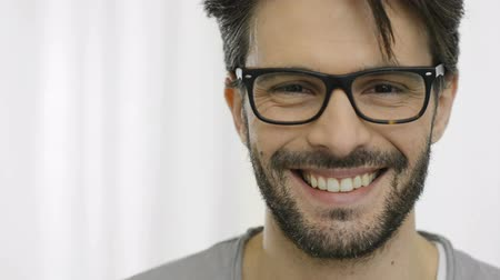 spojrzenie : Closeup of smiling young man wearing eyeglasses. Portrait of happy guy with eyeglasses looking at camera. Close up of a joyful man with beard looking at camera. Wideo