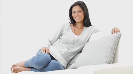 испанец : Beautiful smiling young latin woman at home. Happy girl relaxing and sitting on couch isolated on white background. Portait of smiling woman looking at camera with arm leaning on the sofa