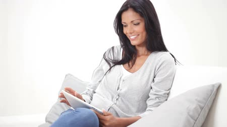 assistindo : Smiling beautiful young woman relaxing with a digital tablet on sofa. Beautiful casual girl sitting on couch and surfing the net with laptop. Happy girl in leisure time at home browsing with computer and looking at camera.