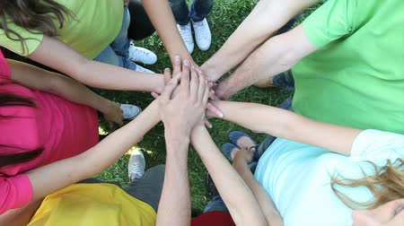yuvarlak : Happy joyful friends forming a circle with their hands in center on grass. Closeup of stack of hands. Teenagers putting their hands on top of each other symbolizing unity and teamwork. Happy Teenage Group with Hands on Stack outdoor. Stok Video
