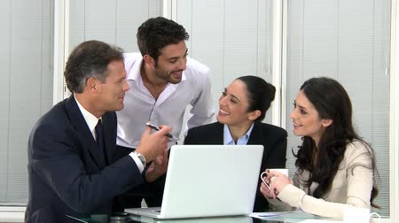 Meeting of businesspeople discuss at the computer. Happy working business team in modern office. Smiling office workers working together at new finical project. Стоковые видеозаписи