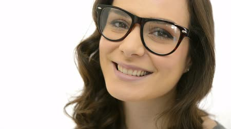 looking : Closeup of smiling young woman wearing eyeglasses. Happy girl with spec isolated on white background. Portrait of beautiful woman with long brown hair smiling and  looking at camera.