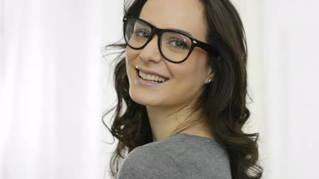 smile : Closeup of smiling young woman looking at camera with eyeglasses. Portrait of happy girl with specs smiling and looking at camera. Pretty woman with long brown hair wearing eyeglasses indoor.