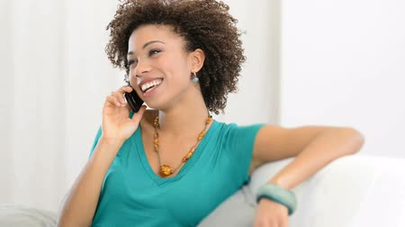 cellphone : Portait of young woman with smartphone looking away. Portrait Of Young Girl Talking On phone Sitting on Couch. Happy girl fun at cellphone. Laughing young african woman smiling at phone.
