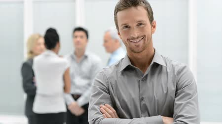 Portrait Of Young Handsome Businessman Smiling In Office. Satisfied guy with arms crossed looking at camera with his colleagues in background. Proud young man smiling in front of his business team. Стоковые видеозаписи