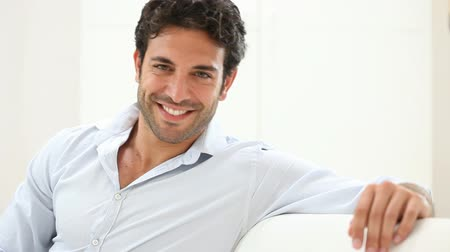 guy home : Happy smiling man relaxing and sitting on sofa at home. Portrait of happy guy smiling and looking at camera on couch. Young man with shirt relaxing at home after work. Stock Footage