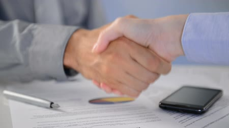 сотрясение : Close Up Of Businesspeople Shaking Hands At Desk.  Close up of business executives shaking hands in an office. Business associates shaking hands in office. Buiness deal.