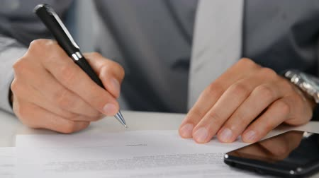 dokument : Close Up Of A Businessman Signing Contract. The male hand signing a business deal in a office. Close up of a signature for a business report. Business worker signing the contract.