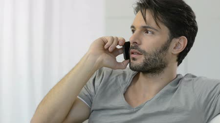 düşünürken : Portrait of thoughtful man talking on cellphone at phone. Serious man talking on phone at home.  Portrait of a worried young  man in casual talking on the phone. Stok Video