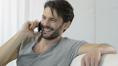 Домашняя жизнь : Portrait of smiling man talking on cellphone at home. Joyful man laughing on phone. Happy young man in casual has an happy conversation at phone. Стоковые видеозаписи