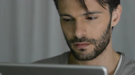 fiatal felnőttek : Closeup Of Person Holding Digital Tablet. A concentrated man surfs the internet at night. Portrait of young man uses the digital tablet to search in the Internet. A student studying with tablet until late.