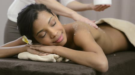 estância termal : Spa therapist applying scrub salt on young woman back at salon  spa.  Beautiful young woman scrubbing body. Body scrub at spa center. Beautiful african woman  gets a salt scrub beauty treatment.