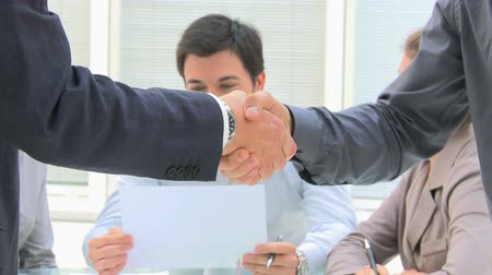 tratar : Business men shaking hands after an agreement during a meeting. Handshake close up with businesspeople in background. Business deal. Handshake between two people for a new deal.