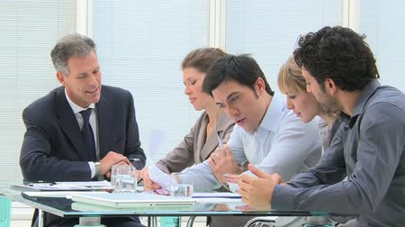 planos : Mature businessman working and discussing with his colleagues at office. Business meeting in a meeting room. Businesspeople discussing in a office with  their colleagues.