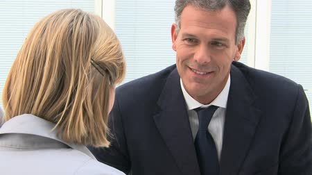 falar : Business colleagues discussing on paperwork in a modern office, Leadership talking with his secretary. Portrait of businessman discussing  with a businesswoman. Happy leadership smiling with his colleague.