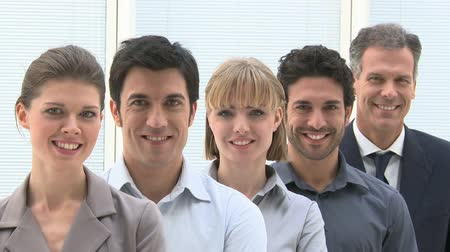 büszke : Happy smiling business team standing in a row at office. Businesspeople looking at camera with satisfaction. Proud businesswomen and successful businessmen standing in a row and looking at camera with a smile. Stock mozgókép