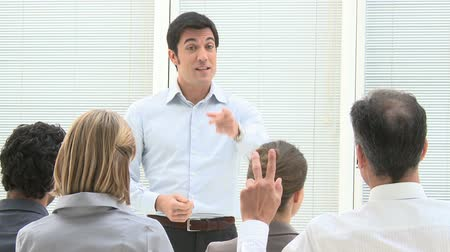 Business consultant answering a question during a meeting at office. Businessman speaks at a business conference and a man raises his hand to ask a question. Business presentation with a business speaker. Стоковые видеозаписи