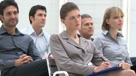 uczenie się : Business group of people attending an educational presentation. Businessmen and businesswomen are concentrated listening to the business conference. Businesspeople sitting at the business meeting.