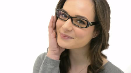 smile : Closeup of smiling young woman wearing eyeglasses. Portrait of happy girl with glasses looking at camera isolated on white background. Casual woman with specs laughing. Stock Footage