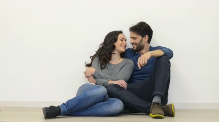 латинский : Portrait of happy young couple sitting On floor looking up ready for your text or product. Smiling coupe in love sitting on floor with copy space. Man and woman embracing in interior. Casual couple looking at camera.