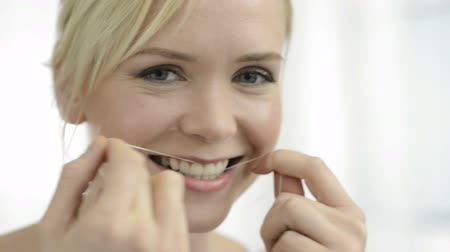 Portrait of young woman flosses her teeth with dental floss and looking at camera. Blonde girl using dental floss. Woman care her teeth with dental floss. teeth cleaning thread. Стоковые видеозаписи