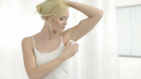 antiperspirant : Portrait of young woman applying deodorant to her armpit. Smiling blonde girl holding a roll-on deodorant in hand. Beauty and skin care concept. A young woman showing her armpit and looking at camera indoors.