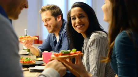 Happy young friends eating bruschetta in kitchen. Young man and woman at home eating at dinner time. Smiling friends have fun and talking while they eat italian food.