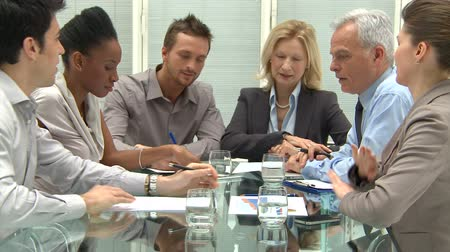 sala de reuniões : Group Of Coworkers Discussing In Conference Room. Businessmen and businesswomen at business meeting in a conference room. Group of businesspeople working together at new project with document and business reports.