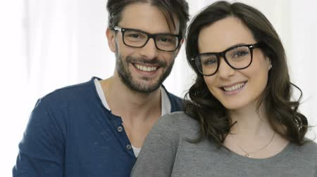 genç çift : Closeup of smiling couple wearing spectacle. Happy young couple in love looking each others and smiling. Man and woman with eyeglasess looking at camera and smiling. Portrait of young couple in casual looking at camera with specs. Stok Video