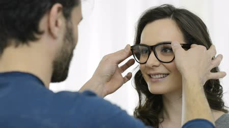 optyk : Optician putting a new pair of eyeglasses on a patient. Young smiling woman tries a new pair of eyeglasses. Portrait of a beautiful girl while the optician puts glasses. Wideo