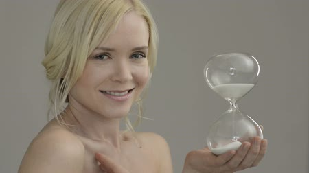 уход за кожей : Beauty portrait of beautiful caucasian woman holding hour glass sand timer, aging process concept. Beauty treatment against skin aging. Portrait of blonde and smiling young  woman holding an hourglass. Concept of time passing.