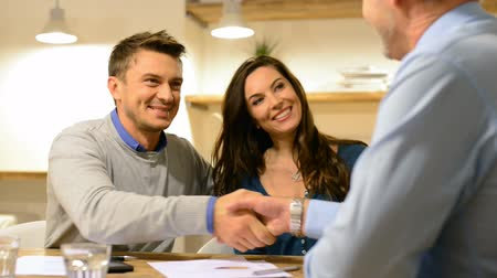 három ember : Couple in real estate agency talking to businessman. Portrait of happy couple talking to a financial consultant to invest their savings.  Couple talking about the financial contract.