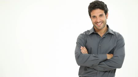 büszke : Casual young man looking at camera with arms crossed and satisfaction. Portrait of happy guy smiling isolated on white background. Satisfied man walking and posing on white background. Stock mozgókép