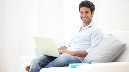 kipiheni magát : Happy smiling young man watching and working on computer at home. A guy surfing the internet with laptop and sitting on the sofa at home. A relaxed man checks the email and the social network. Stock mozgókép