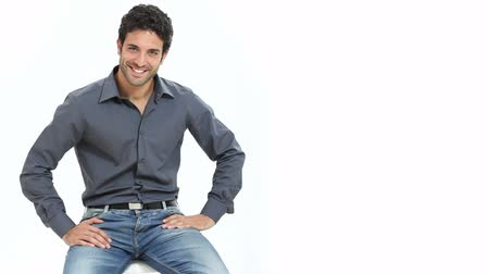 fiatal felnőttek : Satisfied and proud young man sitting on chair and looking at camera isolated on white background. Portrait of happy smiling guy with shirt and jeans looking at camera with copy space. Stock mozgókép