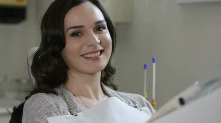 зубы : Smiling young woman receiving dental checkup. Portrait of a smiling woman looking at camera after visiting  the dentist. Woman at dental clinic. Dental care concept.