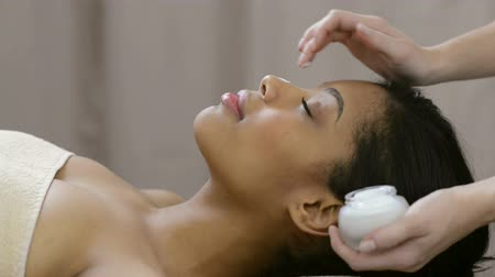 masaż twarzy : Closeup of young woman receiving professional head massage at spa. African woman standing on table massage and receiving a face treatment with moisturizer. Relaxed woman at spa receiving a face massage.