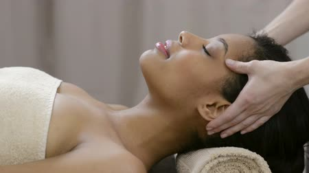 mimos : Closeup of young woman receiving professional head massage at spa. African woman standing on table massage and receiving a face treatment. Relaxed woman at spa receiving a face massage.