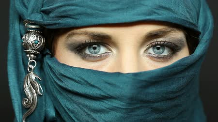 bez : Portrait of an arabic young woman with her beautiful blue eyes in traditional islamic cloth niqab. Close up of beautiful of a muslim woman looking at camera.