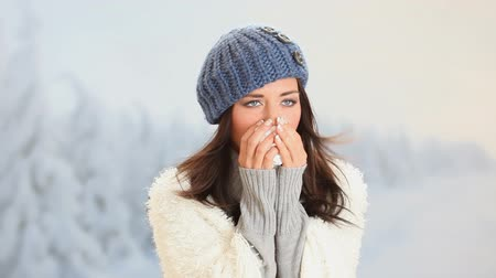 nariz : Pretty girl has flu and fever in winter day outdoor. Portrait of beautiful young woman with wool blue cap  looking at camera with snowy landscape behind.