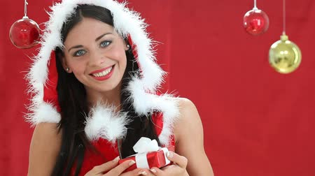 Санта шляпе : Surprised sexy santa claus. Happy joyful young woman in Santa Claus clothes holding a red gift. Portrait of santa girl holding a wrapped gift for christmas and looking at camera with surprised. Стоковые видеозаписи
