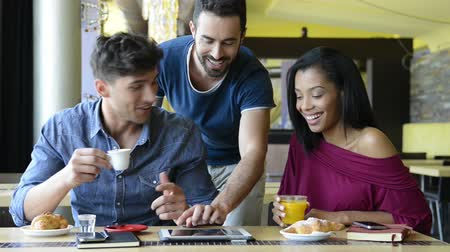 Closeup shot of happy young friends using digitaltablet during breakfast. Smiling men and woman doing breakfast at coffee bar. Happy young friends looking at palmtop and having a joyful breakfast.