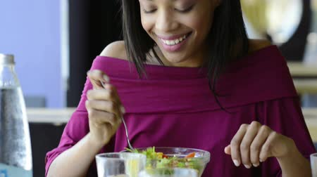 Closeup shot of young woman eating fresh salad at restaurant. Healthy african girl eating salad and looking away. Smiling young woman holding a forkful of salad. Health and diet concept. Woman ina a lunch break. Стоковые видеозаписи