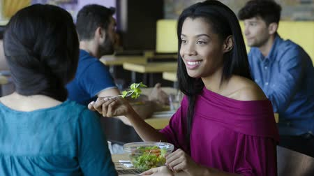 ресторан : Closeup shot of young woman eating salad with her friend. African girl smiling at lunch. Lughing woman eating salada at restaurant during her lunch break.