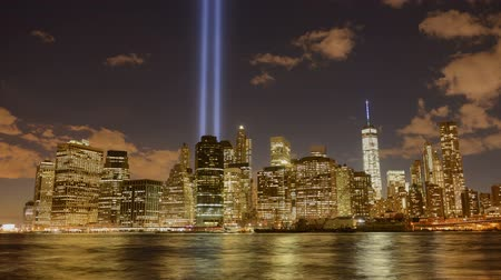 once : Lapso de tiempo 4K video del Tributo en Luz para conmemorar el 11 de septiembre de vista del distrito financiero, Manhattan, Nueva York. Timelapse video de Lower Manhattan horizonte de DUMBO en Brooklyn durante 911, zoom. Dos haces de luz sobre la ciudad de Nueva York.